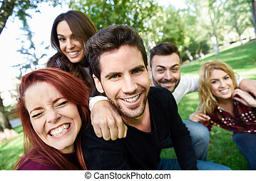 Group of friends taking selfie in urban background. Five...
