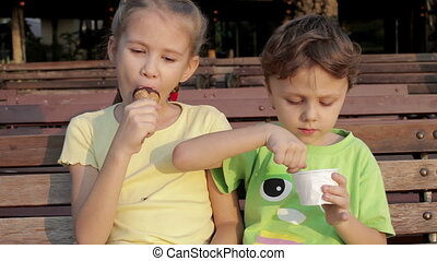 Two happy children eating ice cream on bench