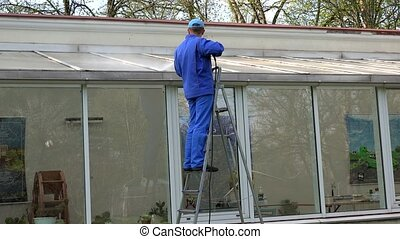 man cleaning glass house roof with high pressure tool in nature.