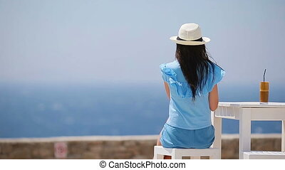 Young girl drinking cold coffee enjoying sea view. Beautiful...