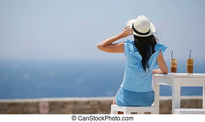 Young woman drinking cold coffee enjoying sea view....