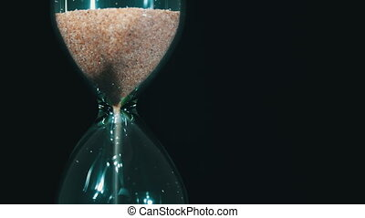 Hourglass on a Black Background, the sand Falls Inside -...