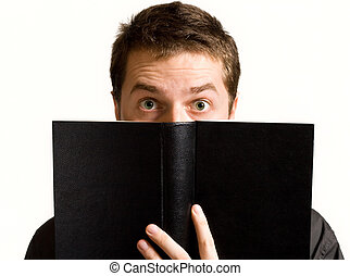 Eyes of surprised man above black book isolated on white