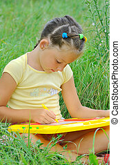 girl draws sitting on a green meadow in the park