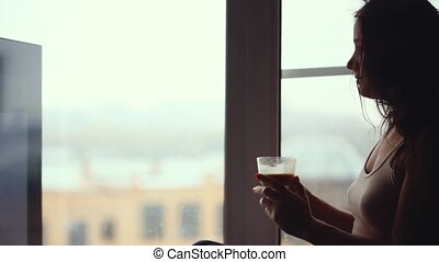 Pretty shaggy woman drinking coffee and looking in window...