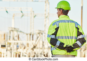 Service engineer standing in front of electro power plant -...