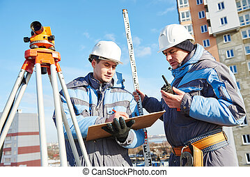 Surveyor workers with level at construction site - two...