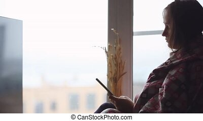Frustrated sad woman in plaid sitting on a window sill...