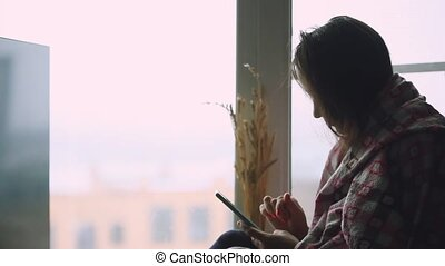 Sad thoughtful woman in plaid sitting on a window sill looking in window while using mobile phone.