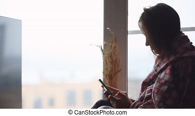Sad woman in plaid sitting on a window sill looking in...