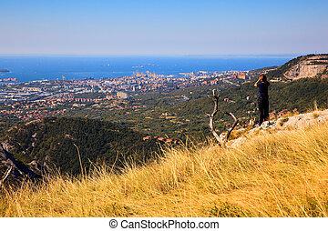 Hiker looking in binoculars enjoying spectacular view on...