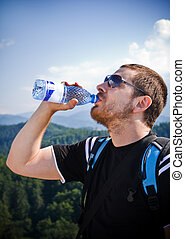 Handsome man drinking water on top of mountain