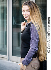 Beautiful successful businesswoman in front of office...