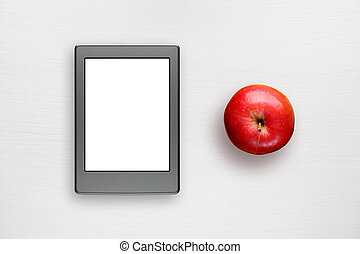 Electronic book and apple on white table