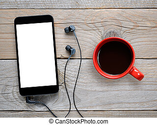 Smartphone with headphones and coffee cup on wooden table...