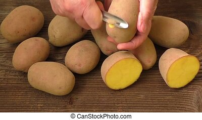 Hands peeling potatoes, top view