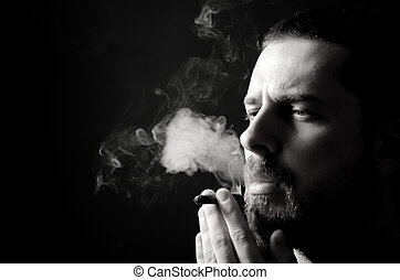 Male smoker in the dark - Black and white portrait of...