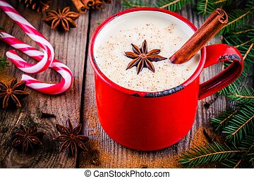 Christmas drink: eggnog with cinnamon and anise in red mug...