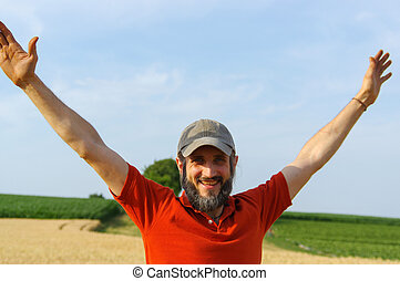 happy bearded man raised up his hands to the sky in a golden summer corn filed, with open arms.