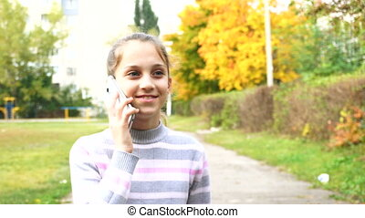 Teen girl talking by her smartphone in autumn park
