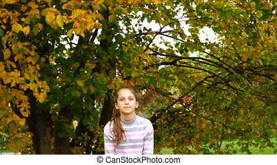 Teen girl throwing leaves in slowmotion - Teen girl throwing...