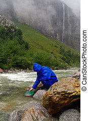 prospector panning gold in a river with sluice box on  rainy day