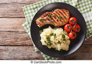 Grilled pork loin with mashed potatoes and tomato close-up. Horizontal top view
