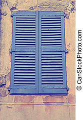 Vintage blue close window with shutters in old stone house,...