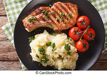 Grilled pork T-bone steak garnished with mashed potatoes close-up. Horizontal top view
