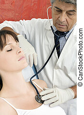 man doctor visits a young caucasian woman with stethoscope