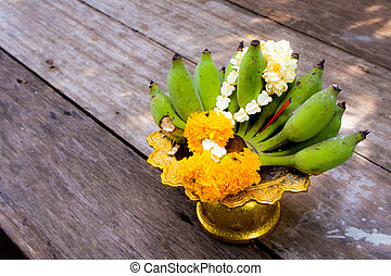 Flower garlands and banana on pedestal tray