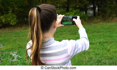 Teen girl doing photos of nature in autumn. Outdoor.