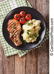 Grilled pork loin with mashed potatoes and tomato close-up. Vertical top view