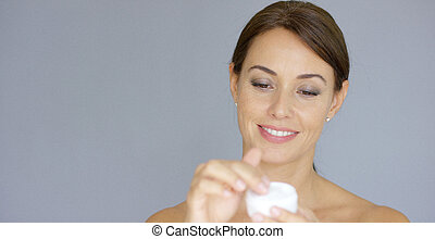 Gorgeous young woman applying face cream from a handheld jar...