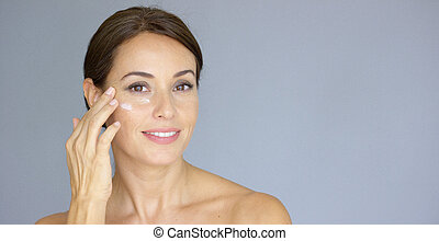 Beautiful young woman applying face cream to her cheek bone...