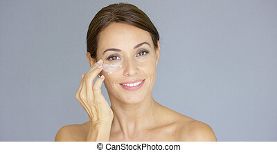 Gorgeous young woman applying face cream to her cheek with...