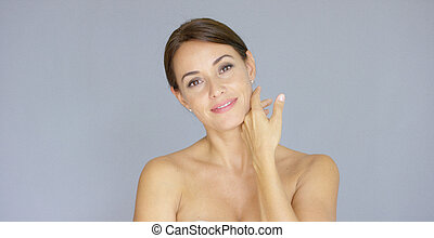 Pretty bare shouldered woman with fingers on neck - Pretty...