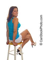 Perched on Stool - Pretty young lady in shorts perched on...