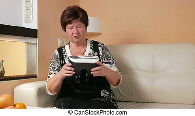 Woman aged acquainted with virtual reality goggles. She brings points to the head and twists in different directions. Hands trying to touch the invisible things