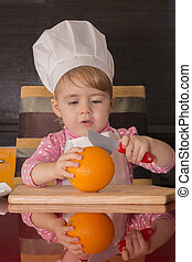 little cute kid in a cook cap on kitchen cuts oranges. Mother's helper. 2 year old.