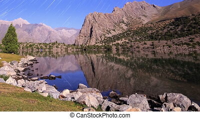 Moonlight over a lake. Traces of stars similar to metory. Time Lapse. Pamir, Tajikistan