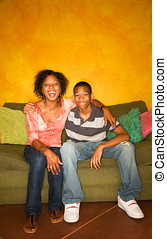 African-American woman and teen on green sofa - Good-looking...
