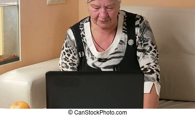Woman aged working on laptop at home on the couch. She...