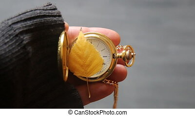 November idea. Gold pocket watch and autumn leaf. - Hand...
