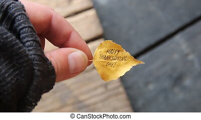 autumn leaf with text Happy Thanksgiving day - hand holding...
