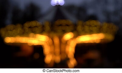 Illuminated retro carousel at night. Blurred - Illuminated...