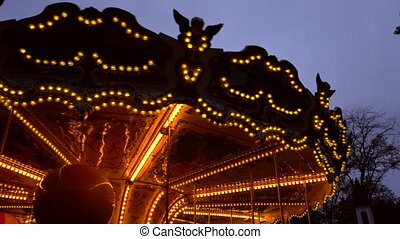 Illuminated retro carousel at night in the city park