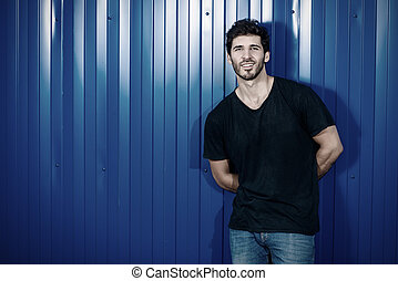 man by a blue fence - Attractive masculine man standing on a...