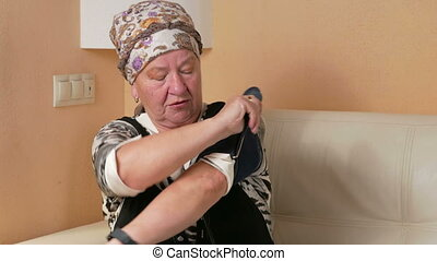 Woman aged measures the blood pressure at home. She wears a...