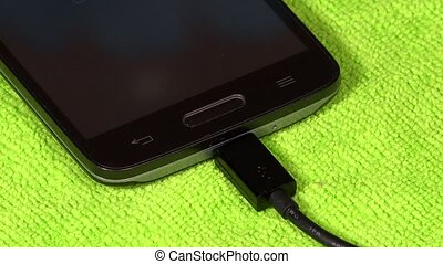 female hand unplug black cable from smart device on green background